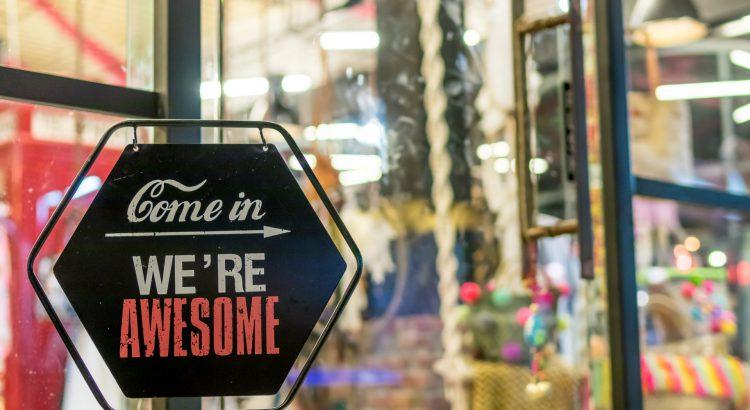 """fachada de loja com placa em inglês que diz """"entre, somos incríveis"""""""